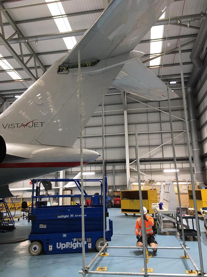 Scaffold being built under plane